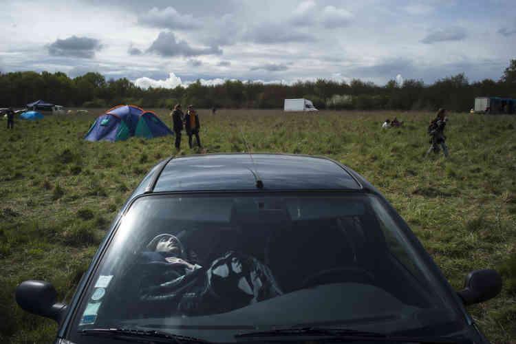 Un teknivalier dort dans sa voiture, à proximité d'une scène qui diffuse de la hardcore, un style de techno qui empêcherait beaucoup de dormir.