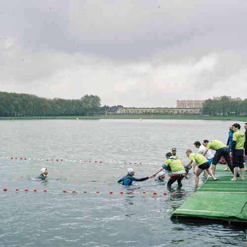 Dans le parc du château de Versailles (Yvelines), des participants au Triathlon du Roi sortent de la pièce d'eau des Suisses.