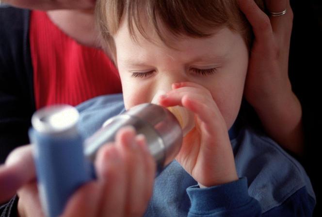 Un enfant asthmatique inhale de la Ventoline.