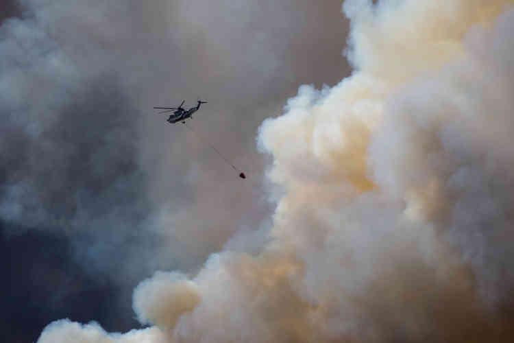 Un hélicoptère tente d'éteindre l'incendie de Fort McMurray une ville de 100 000 habitants en Alberta.