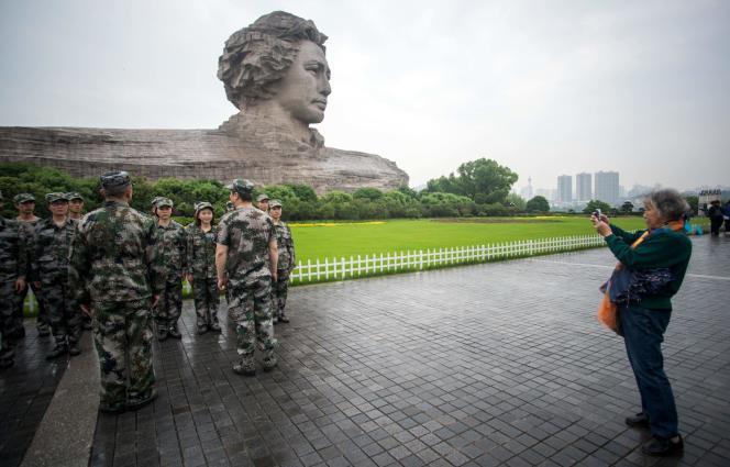 Des soldats de l'Armée populaire de libération posent devant une statue de Mao jeune, le 22 avril 2016 àChangsha, la capitale de la province du Hunan.