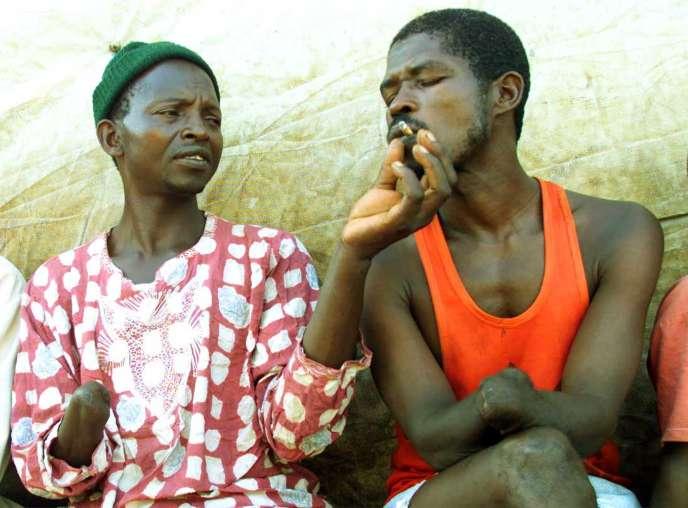 Dans un centre pour personnes amputées de Freetown, capitale de la Sierra Leone, deux amis partagent une cigarette, en mai 2000.