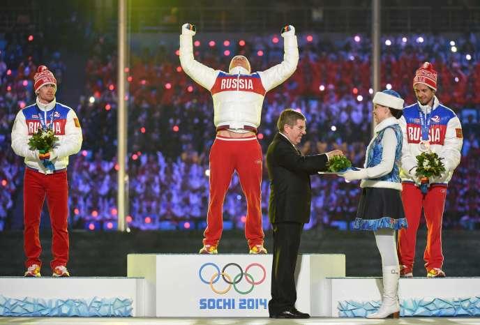 Thomas Bach, le président du CIO, remet les médailles aux athlètes du podium 100 % russe du 50 km de ski de fond, aux JO de Sotchi, le 23 février 2014.