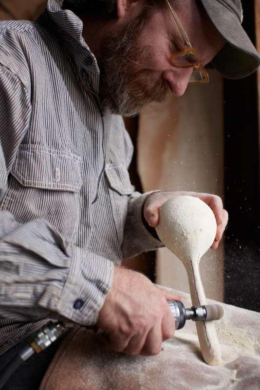 Joshua Vogel, artisan et sculpteur, fabrique des cuillères en bois dans son atelier.