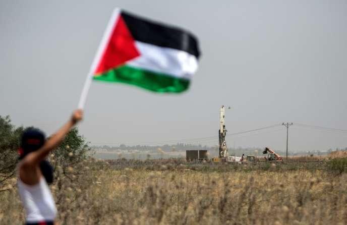 Un jeune Palestinien agite un drapeau devant des militaires israéliens à la frontière est de Gaza, le 15 mai, 68e anniversaire de la création de l'Etat d'Israël. Jour de la« Nakba», la« catastrophe» en arabe.