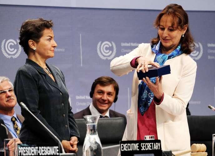 La ministre de l'environnement française, Ségolène Royal (à droite), remet un cadeau à la secrétaire exécutive de la convention-cadre des Nations unies sur les changements climatiques,Christiana Figueres, à Bonn, lundi16mai2016.