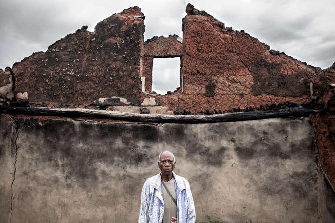 Un habitant pose dans les ruines de sa maison où il tenait une épicerie, en février 2013 à Madagascar.