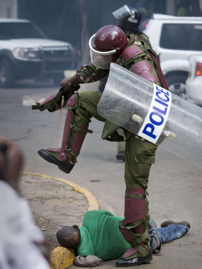 Un policier frappe un manifestant à terre, le 16 mai, à Nairobi, capitale du Kenya.