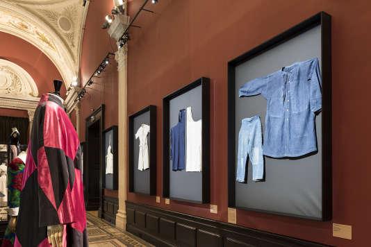 Le manteau de Schiaparelli face à des vêtements de travail encadrés.
