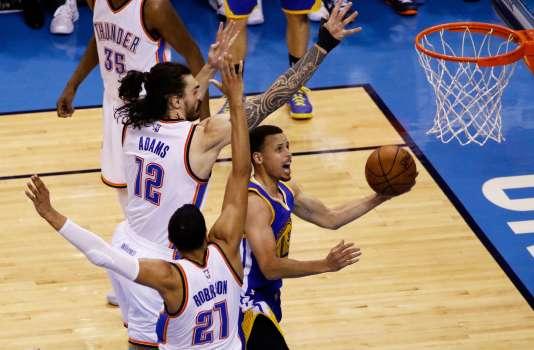 Stephen Curry (en bleu au centre) des Golden State Warriors au duel avec Steven Adams (en blanc, numéro 12) des Oklahoma City Thunder lors du troisième match de la finale de conférence Ouest.