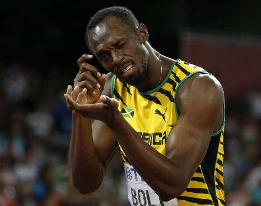 L'athlète jamaïcain Usain Bolt fait mine de prendre en photo les photographes lors des championnats du monde d'athlétisme 2015 à Pekin.