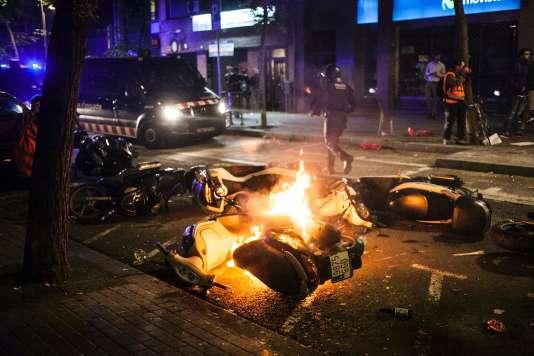Des véhicules incendiés dans le quartier de Gracia, à Barcelone, le 23 mai 2016, après des manifestations contre la fermeture d'un squat.