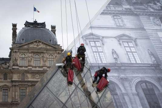 Collage de l'anamorphose de JR sur la Pyramide du Louvre le 24 mai, veille de l'inauguration de l'installation.