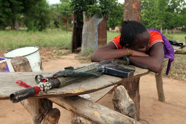 Dans l'Etat de Benue, une villageoise dort à côté de l'arme de son mari, membre d'une milice créée pour se défendre face aux Peuls.