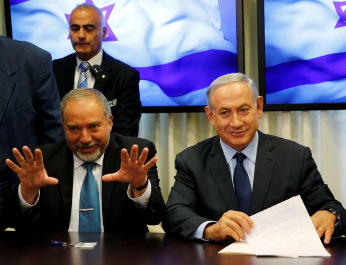 Avigdor Lieberman, le chef du parti d'extrême droite israël Beitenou (à gauche), est assis à côté du premier ministre israélien Benyamin Nétanyahu, lors de la signature d'unaccord de coalition pour élargir la majorité parlementaire du gouvernement, à la Knesset, le parlement israélien.