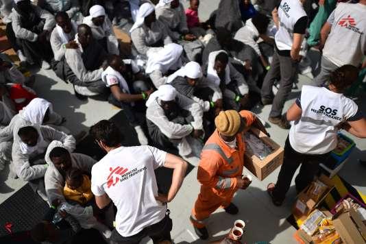 Des membres de Médecins Sans Frontières et de SOS Méditérannée distribue de la nourriture aux réfugiés du navire« Aquarius».