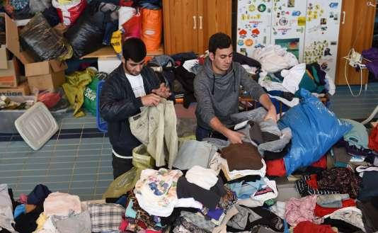 Des immigrants irakiens choisissent des vêtements parmi les dons apportés à l'eglise Saint Joseph de Tutzing, le 24 mai 2016.