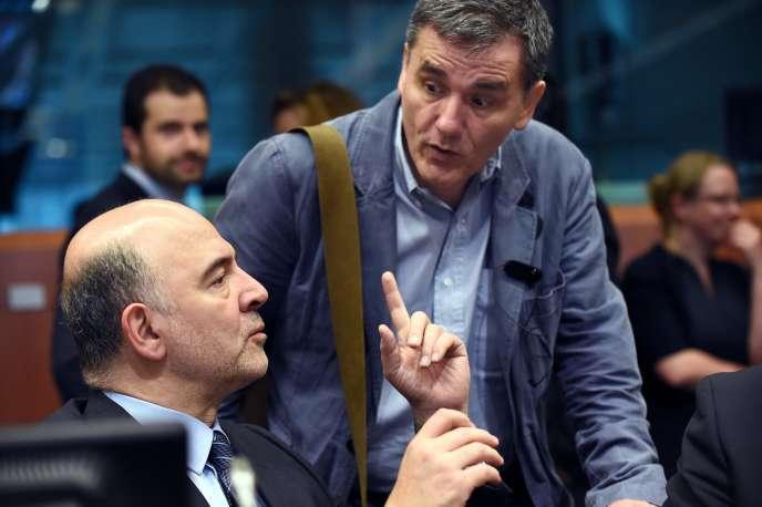 Pierre Moscovici, commissaire européen à l'économie, et Euclide Tsakalotos, ministre grec des finances, à Bruxelles, le 24mai.