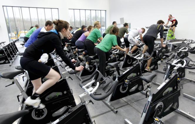Salle de biking en groupe, en musique et anime par un coach dans un club de remise en forme à Lille.