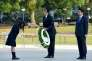 CORRECTION / US President Barack Obama (C) recieves a wreath from a student (L) beside Japanese Prime Minister Shinzo Abe (R) at the cenotaph in the Peace Momorial park in Hiroshima on May 27, 2016. Obama on May 27 paid a moving tribute to victims of the world's first nuclear attack. / AFP / TOSHIFUMI KITAMURA