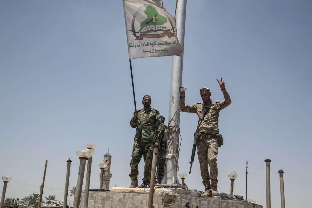 Des miliciens chiites brandissent leur drapeau sur une place de Garma.La bataille de Fallouja pourrait durer des semaines ou plus d'un mois. Une victoire pourrait éloigner la menace d'attentats à Bagdad, qui se sont multipliés au printemps, alors que la capitale irakienne est située à seulement 60 km.