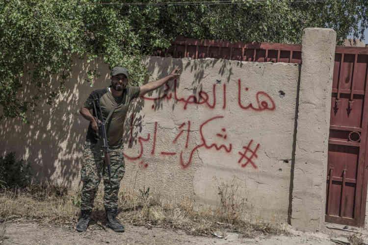 Sur un mur de Garma, dans la province sunnite de l'Anbar, un milicien chiite devant des inscriptions « IciAl-Asaeb» – en référence à la milice chiite Asaeb Al-Aq – et « Merci l'Iran».