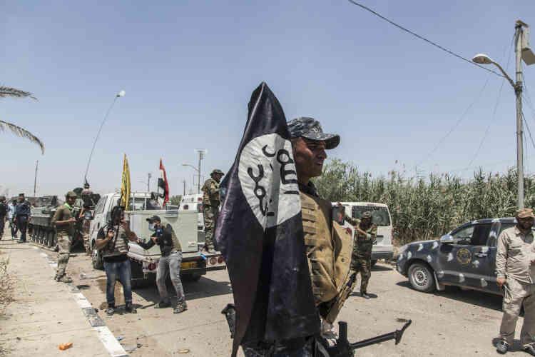 Un milicien chiite rapporte un drapeau de l'organisation Etat islamique (EI). Depuis le 23 mai, les milicesse sont lancées dans la bataille de Fallouja aux côtés de l'armée, de la police fédérale, de l'unité antiterroriste, de forces tribales sunnites et de la coalition internationale contre l'EI, dirigée par les Etats-Unis.