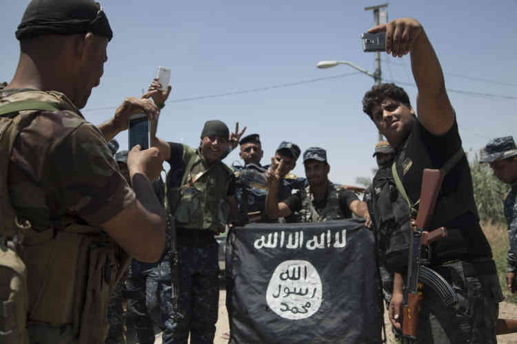 Des miliciens chiites se photographient devant un drapeau pris à l'EI.