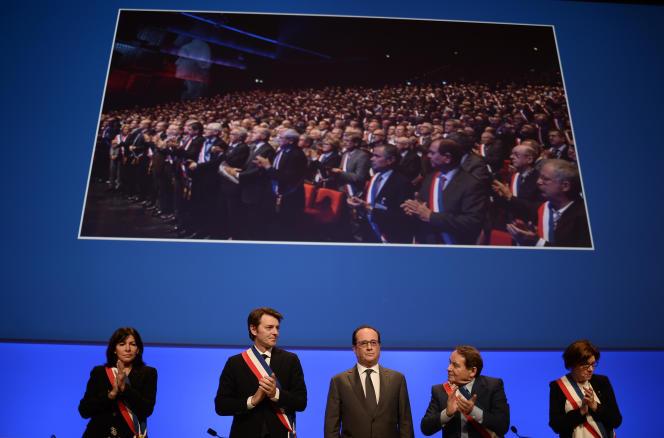 La maire de Paris Anne Hidalgo (à gauche), le président de l'association des maires de France et maire de Troyes Francois Baroin(deuxieme à gauche), le président francais Francois Hollande (au centre) et le vice-president de l'AMF et maire d'Issoudun Andre Laignel (deuxieme à droite) lors du rassemblement des maires de France, à Paris, le 18 novembre 2015.