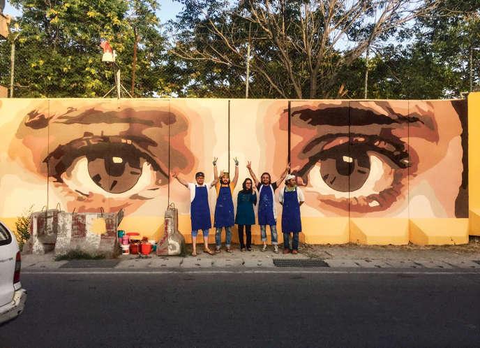 Kabir Mokamel (deuxième en partant de la gauche) avec des membres de son collectif d'artistes devant son premier graffiti, « Je vous vois », qui fait allusion à la corruption dans le pays.