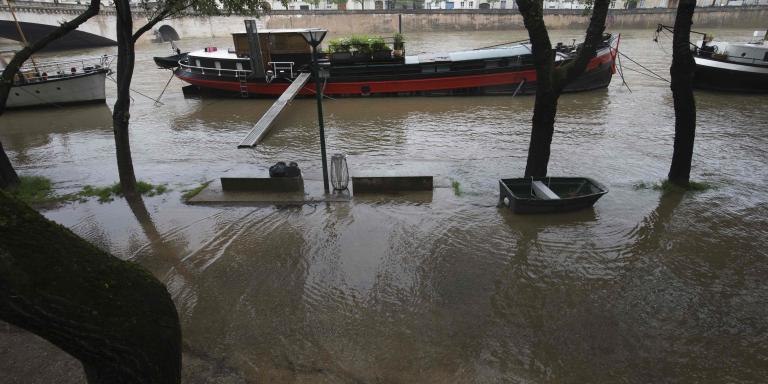 This photo shows barges on the river Seine on Quai de la Tournelle after its banks became flooded following heavy rainfalls on May 31, 2016 in Paris. France's weather agency Meteo France maintained today 18 departments under orange alert for heavy rainfalls, which have already disrupted transports in the northeastern part of the country. / AFP / JOEL SAGET