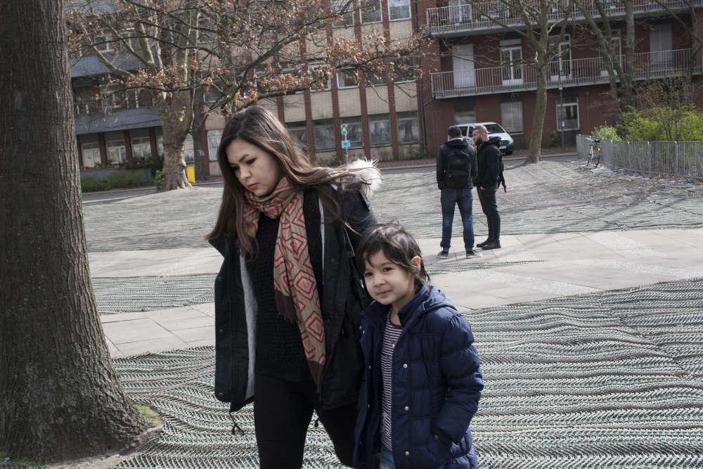 Marzieh à l'entrée de LaGeSo, les services sociaux, dans le quartier Moabit de Berlin, où elle vient chercher sa pension une fois tous les trois mois, avec sa fille Hasti, agée de 6ans.