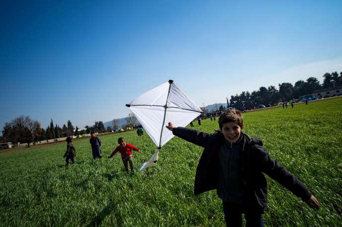 Des enfants jouent dans un champ, à proximité du camp de réfugiés d'Idomeni, à la frontière gréco-macédonienne, le 19 mars 2016.