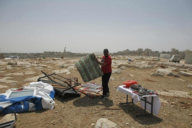 Un Palestinien rassemble ses affaires après le démantèlement par Israël de préfabriqués, à Al-Eizariya, le 16 mai.