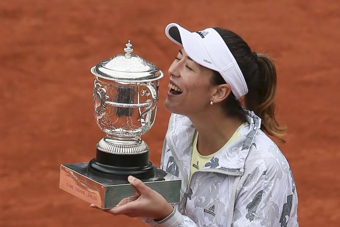 Garbine Muguruza, sourire aux lèvres, avec son trophée, après avoir remporté la finale de Roland-Garros face à Serena William, samedi 4 juin.