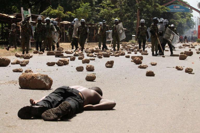 Un groupe de policiers anti-émeutes devant l'un des deux manifestants tués, lundi 6 juin, à Kisumu (Kenya) au cours des manifestations organisées par l'opposition pour réclamer ladissolution de la commission électorale.