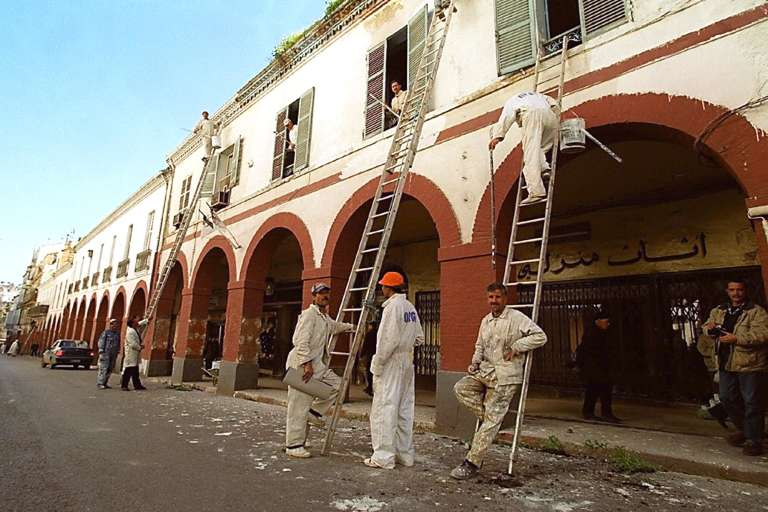 Des ouvriers rénovent des bâtiments à Constantine en 2000.