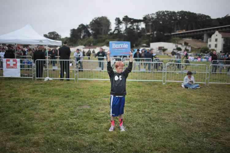 Un jeune supporteur attend que le sénateur monte sur scène lors du rassemblement à la base militaire Presidio.
