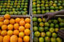 An employee puts an orange on a fruit rack at a Foodmart Fresh supermarket in Jakarta, Indonesia June 8, 2016. REUTERS/Beawiharta