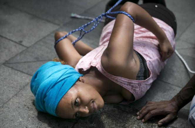 Une migrante d'Erythrée en Israël simule ce qu'elle décrit comme une technique de torture lors d'une manifestation devantl'ambassade de l'Union européenne à Tel Aviv, en juin 2015.