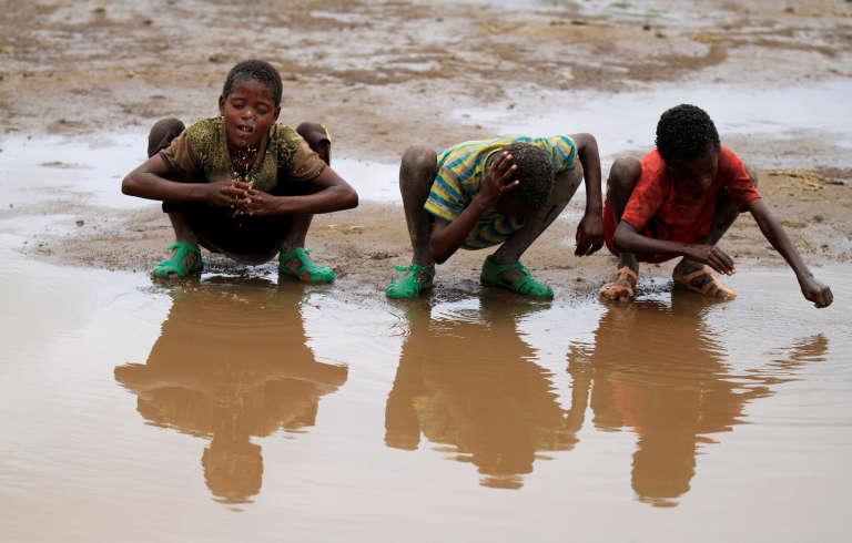 Des enfants se lavent les mains dans une flaque près du village de Kobo, dans la région d'Oromia