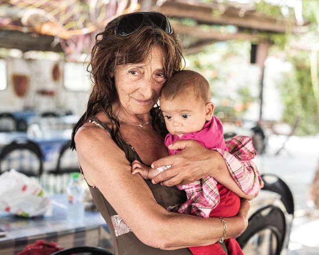 Matina Katsiveli, le pilier de l'assistance humanitaire à Leros, avec un bébé de réfugié, en mai 2016.