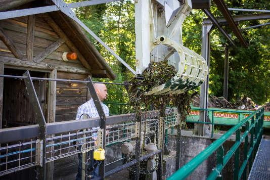 Eric Javanaud, garde-rivière, fait fonctionner le dégrilleur pour retirer les déchets des grilles de protection. Derrière lui, un chalet de télégestion, bassin de Vilgénis (Massy).
