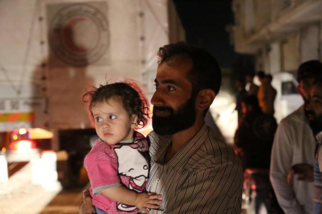 Des habitants de Daraya attendent près du convoi de nourriture.