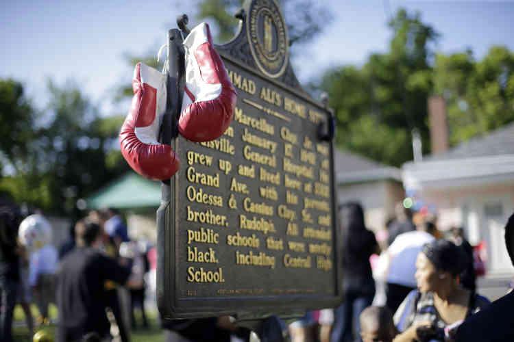 Des gants de boxe accrochés par des fans sur une plaque commémorative devant son ancienne maison à Louisville, où il agrandi en pleine ségrégation raciale.