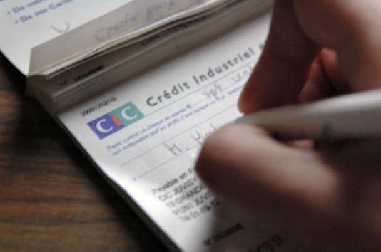 Le titulaire d'un compte au CIC remplit un chèque.