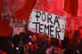 """A demonstrator, holding a sign with a message that reads in Portuguese; """"Temer out"""", takes part in a rally in support of Brazil's suspended President Dilma Rousseff and against acting President Michel Temer in Sao Paulo, Brazil, Friday, June 10, 2016. Rousseff is suggesting she would hold a national referendum on her presidency if she survives an impeachment trial expected for August. Rousseff was impeached and suspended May 12. She is accused of using illegal accounting techniques hide large federal budget deficits. (AP Photo/Andre Penner)"""