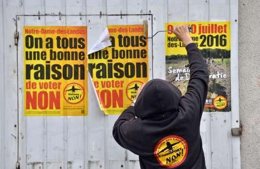 Un militant colle des affiches contre l'aéroport deNotre-Dame-des-Landes, le 13 juin.