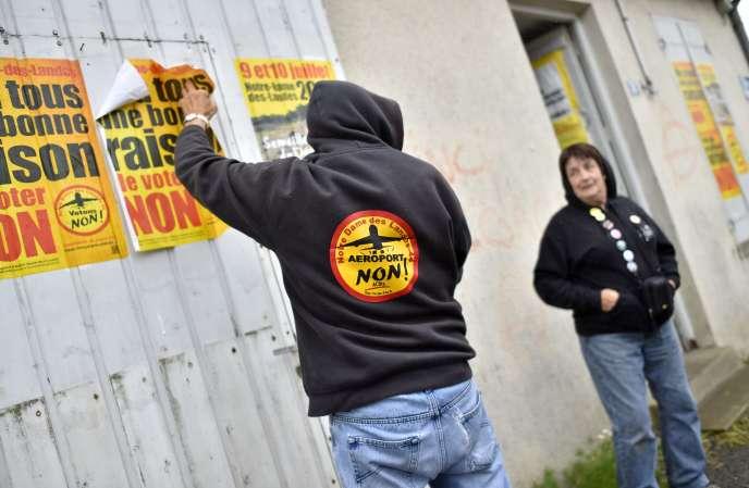 Un militant colle des affiches pour le « non » au futur aéroport de Notre-Dame-des-Landes, le 13 juin.