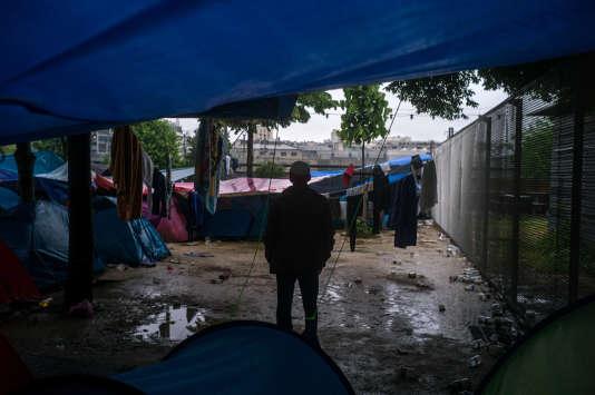 Un réfugié se tient debout dans le camp de fortune où sont installés une centaine de réfugiés dans le jardin d'Eole, à Paris, le31mai2016.